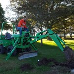 Tom's Heating, Air Conditioning and Plumbing Services - backhoe fixing a waterline.