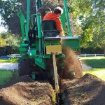 Tom's Heating, Air Conditioning and Plumbing Services - trencher doing a waterline replacement.
